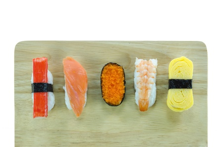 top view Japanese  sushi set on wooden board over white background photo