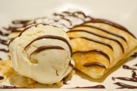 close up vanilla ice cream and crepes with banana , chocolate sauce  served with whipping cream photo