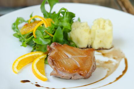 close up  duck breast  served with mashed potatoes , slice of orange and  fresh salad  photo
