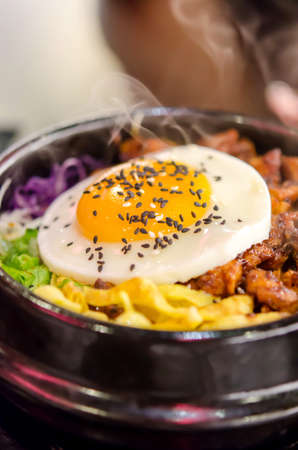 bibimbap in a heated stone bowl ,  korean style food   rice , meat , fried egg and mix vegetable   photo