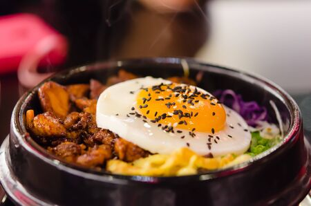 closeup bibimbap with fried egg in a heated stone bowl ,  korean style food photo