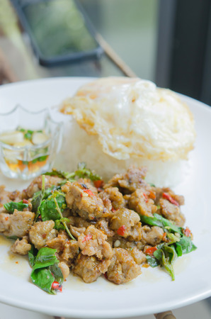 close up stir fried minced pork with chili , sweet basil served with steamed rice,  fried egg and chili sauce on dish photo