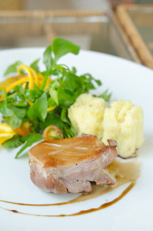Roasted duck breast  served with mashed potatoes , fresh salad  on white plate  photo