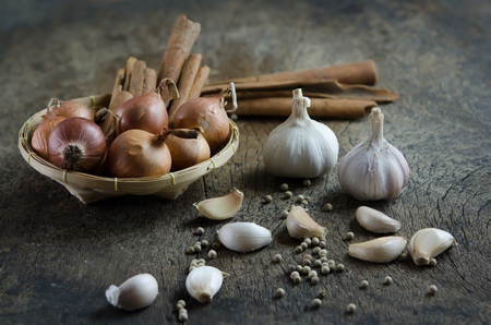 onion and cinnamon stick in basket  , garlic and peppercorns on  wooden board   food ingredients   photo