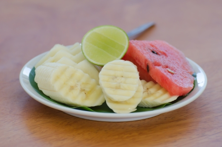 slice of fresh banana and watermelon with lime   on dish over wooden background photo