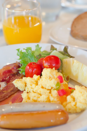 sausage , scrambled eggs , bacon and  fresh vegetable salad on dish photo