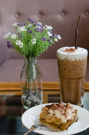 Banoffee pie on white dish with silver fork and ice coffee photo