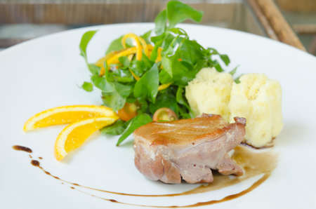 Roasted duck breast  served with mashed potatoes and orange , fresh salad and white wine sauce photo