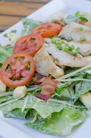 close up ceasar salad  with  slices of grilled pork  photo
