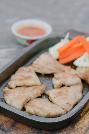 close-up of  grilled pork  served with vegetable and chili sauce photo