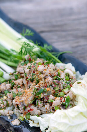 spicy minced pork eaten with fresh vegetable on plate photo