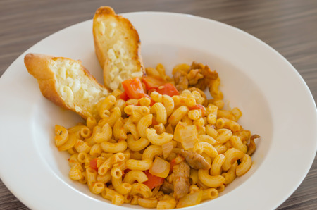 Italian tomato pasta served with garlic bread photo