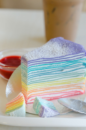 Rainbow crepe cake served with strawberry sauce photo