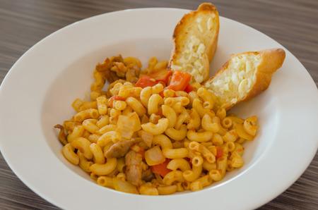 Italian tomato pasta served with garlic bread photo