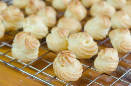 choux: crema fresca choux en una rejilla de enfriamiento sobre la mesa de madera