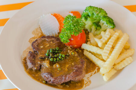 close up beef steak with green peppercorn sauce photo