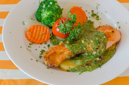 steak of salmon served with green sauce and vegetable on plate photo
