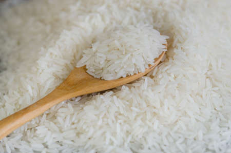 Wooden spoon with rice lying against the background rice photo