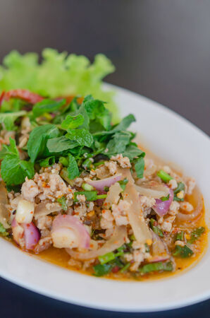 spicy minced pork eaten with fresh vegetable on plate , asian food photo
