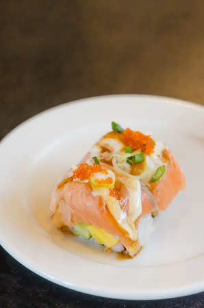 Salmon roll sushi with shrimp egg on top in white dish photo