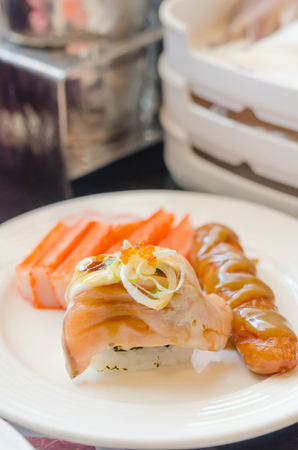 Salmon roll sushi with sausage  and crab strick in white dish photo