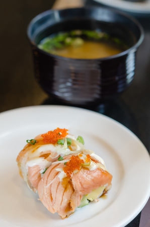 grilled salmon roll sushi with shrimp egg on top in white dish served with miso soup photo