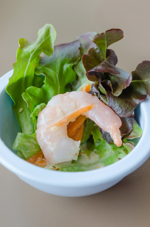 Oak leaf lettuce salad with shrimps in blue bowl photo