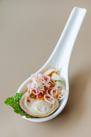 giant mussel with spicy chili sauce on spoon photo
