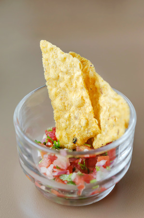 Tortilla chips with salsa dip in cocktail glass photo