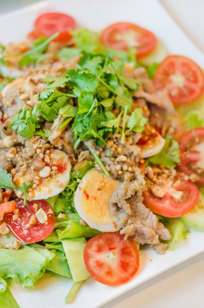 spicy salad with egg , pork and fresh vegetable photo