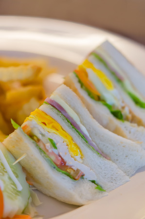 Delicious club sandwich with french fries at a dinner photo