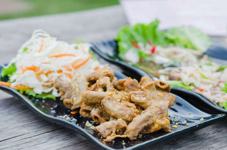 chitterlings: pork chitterlings fried served with fresh vegetable on dish