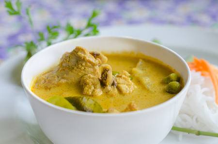 yellow chicken curry in bowl served with fresh vegetable