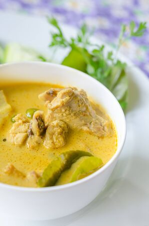 vegetable curry: yellow chicken curry in bowl served with fresh vegetable