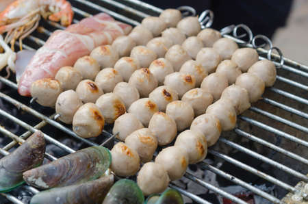 nem: Meatballs on metal skewers being grilled on a barbecue