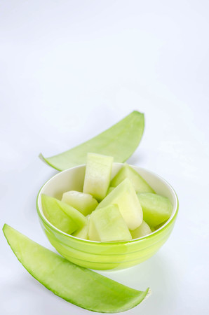 shopped green melon in bowl on white background