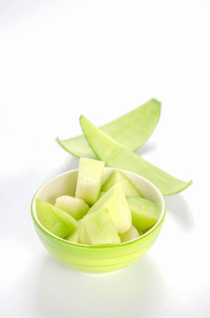 Cantaloupe: shopped green melon in bowl on white background