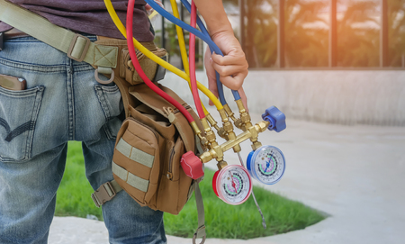 Mano del hombre sosteniendo un manómetro en el equipo para el llenado de acondicionadores de aire Foto de archivo - 86798014