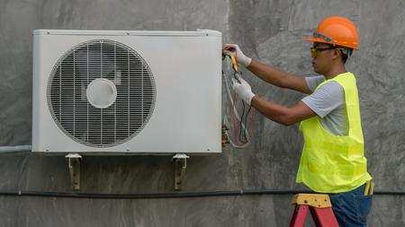 De technicus controleert de openluchtairconditionereenheid