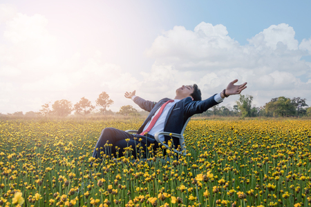 Asian businessman is lying on a chair and open his arm in a large yellow flower field