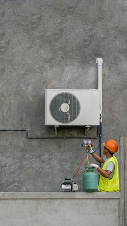 Técnico está verificando unidade de ar condicionado ao ar livre Foto de archivo - 94276375