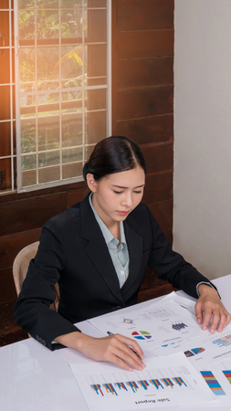 Young asian businesswoman sitting at workplace and reading paper in office