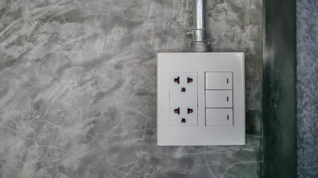 electric plug and switch on gray wall 写真素材