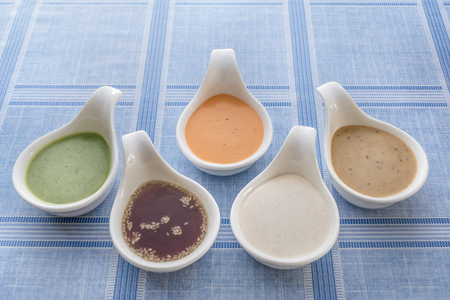 Different homemade cream sauce of salad in spoon