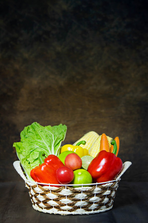 fresh vegetables and fruits in wicker basket over wooden background