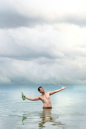 A very happy man  with outstretched arms  in the sea