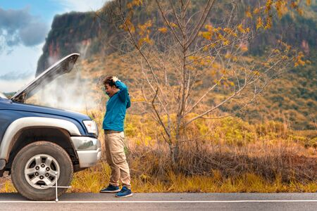 Asian stressed man having trouble with his broken car looking in frustration at failed engine Stock Photo