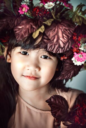 Asian little girl with black hair, dressed in a wreath of flowers on her head Banco de Imagens