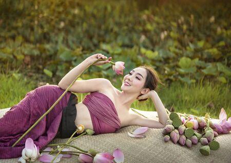 beautiful woman in traditional asian dresses harvesting water lilies in garden Foto de archivo - 128098485
