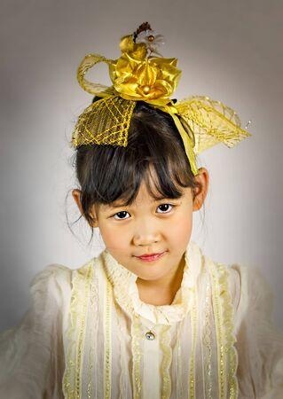 Portrait of asian little girl with golden flower Foto de archivo - 128099357